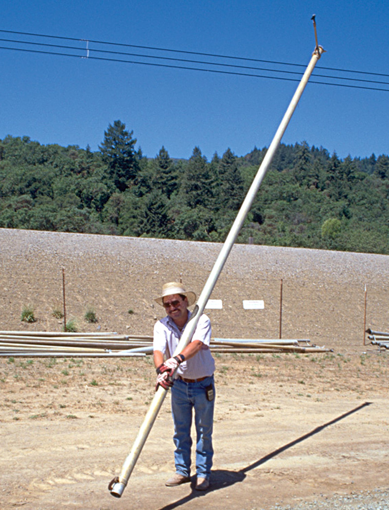 Worker carrying irrigation pipe